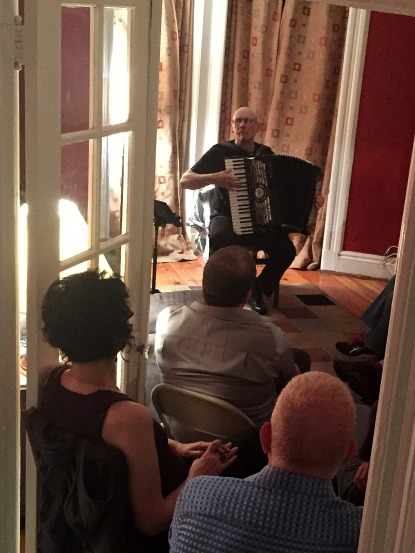 Guy Klucevek, the accordion master, in a home concert hosted by his longtime friend George Russell (below)